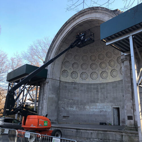 A crane lifts inspectors to the underside of the top of the bandshell