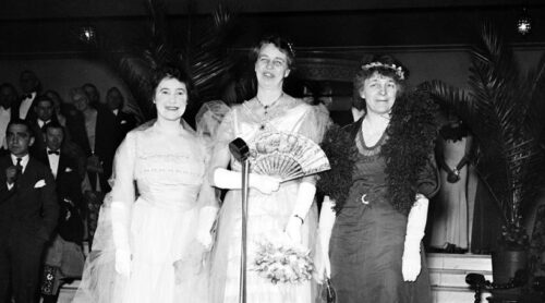 Eleanor Roosevelt is flanked by Rumsey and Greenway in front of a microphone