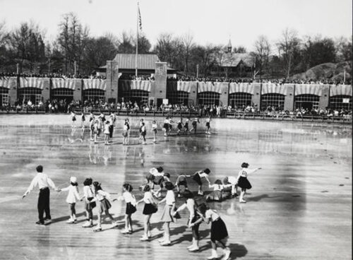 The rink is shot in black and white showing a brick pavilion and skaters in formation