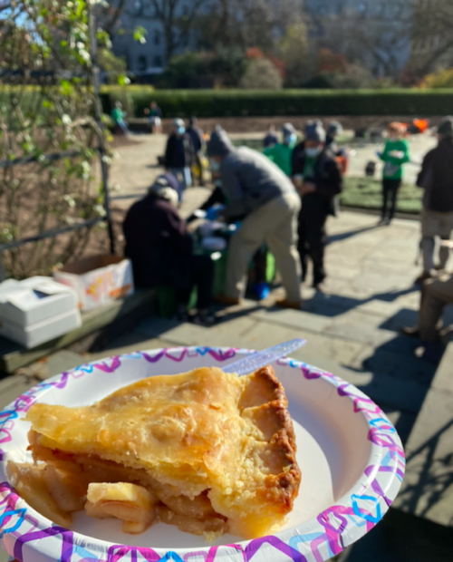 A delicious slice of apple pie on a paper plate, with Conservancy volunteers toiling in the background.