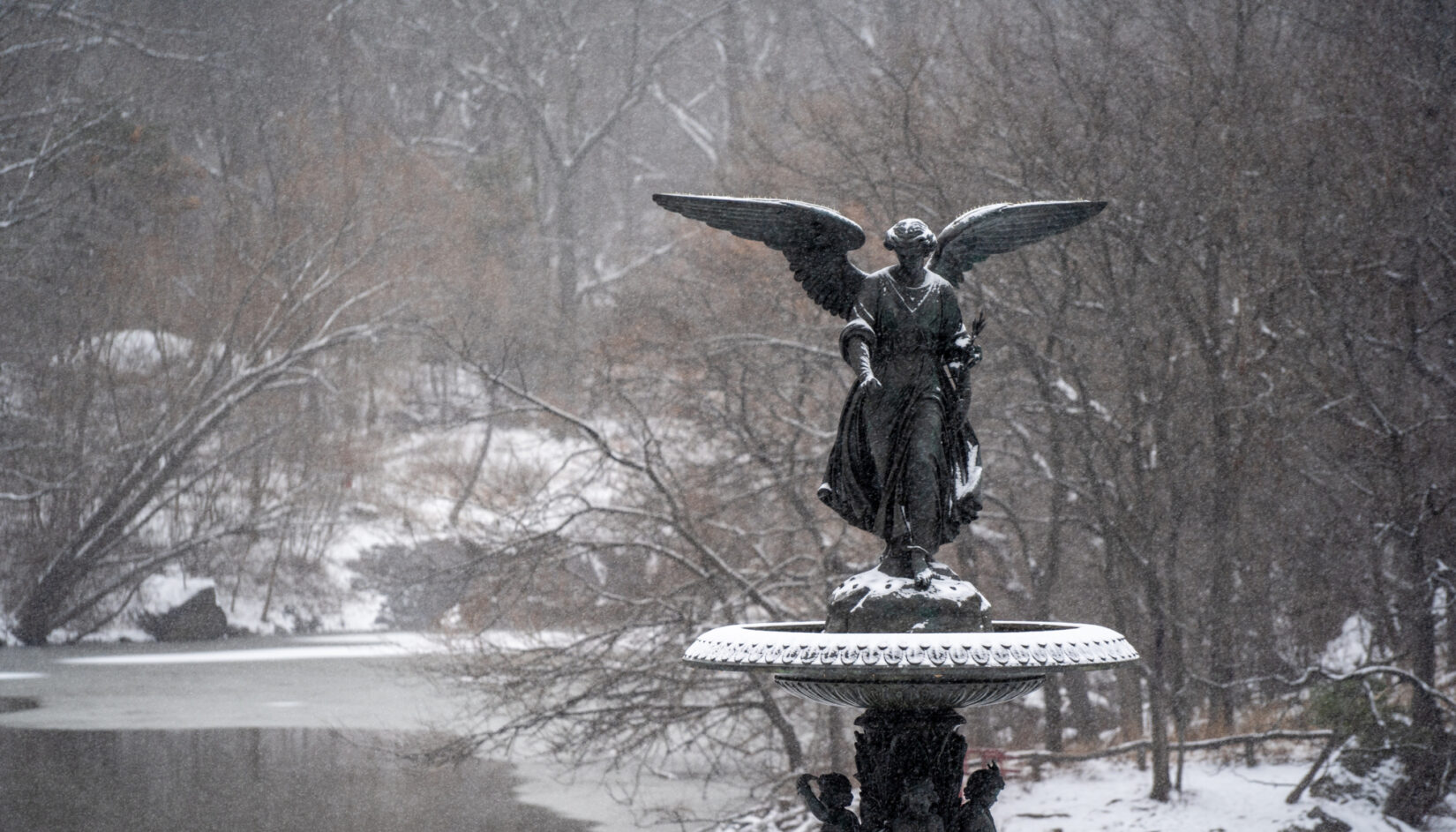 The fountain at Bethesda Terrace, dusted with snow, with the wintery Lake in the background.