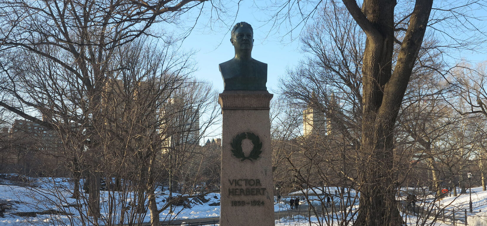 The bust of Victor Herbert sits on a tall pedestal amid a wintery landscape