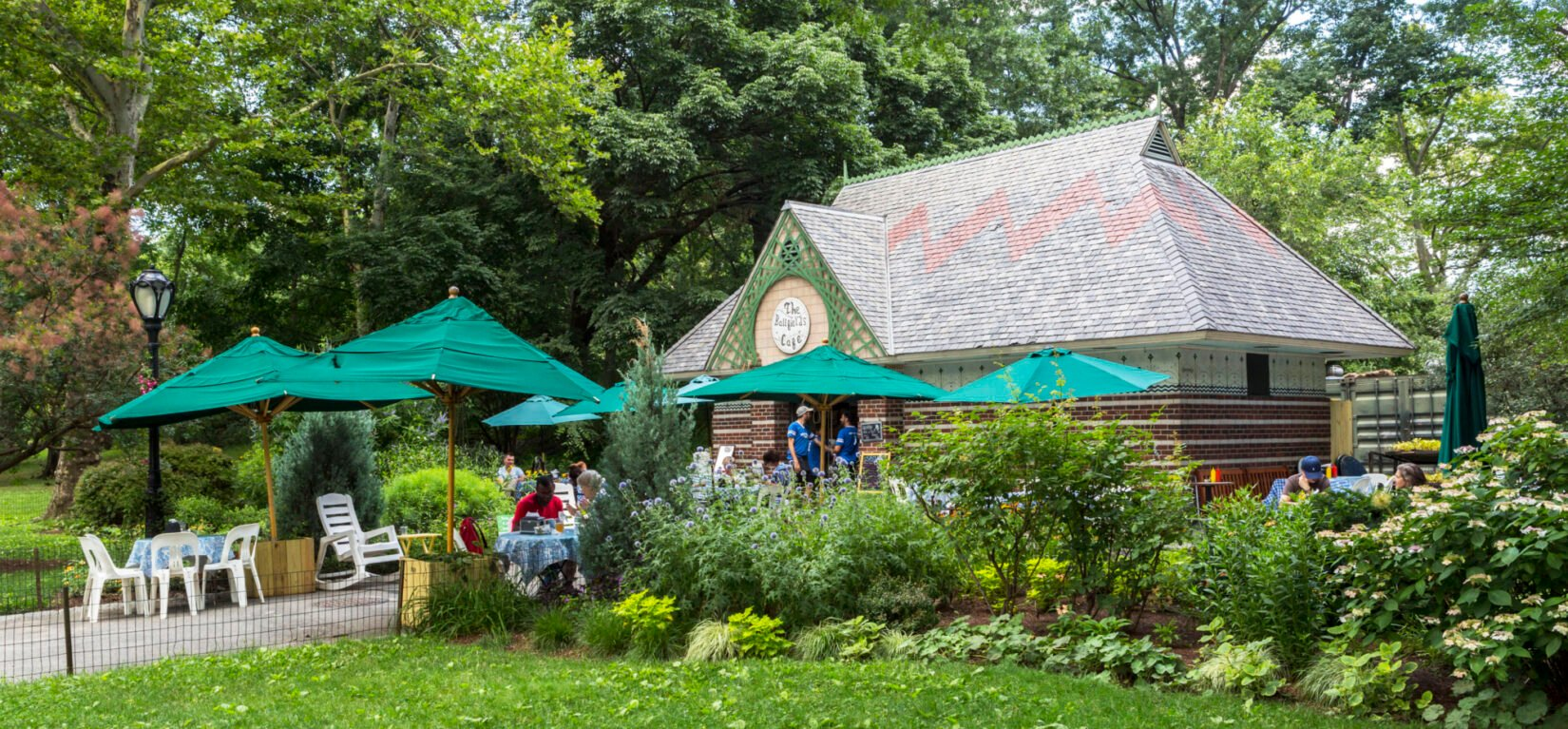 People enjoying cafe fare under green umbrellas in the outdoor dining area of the cafe