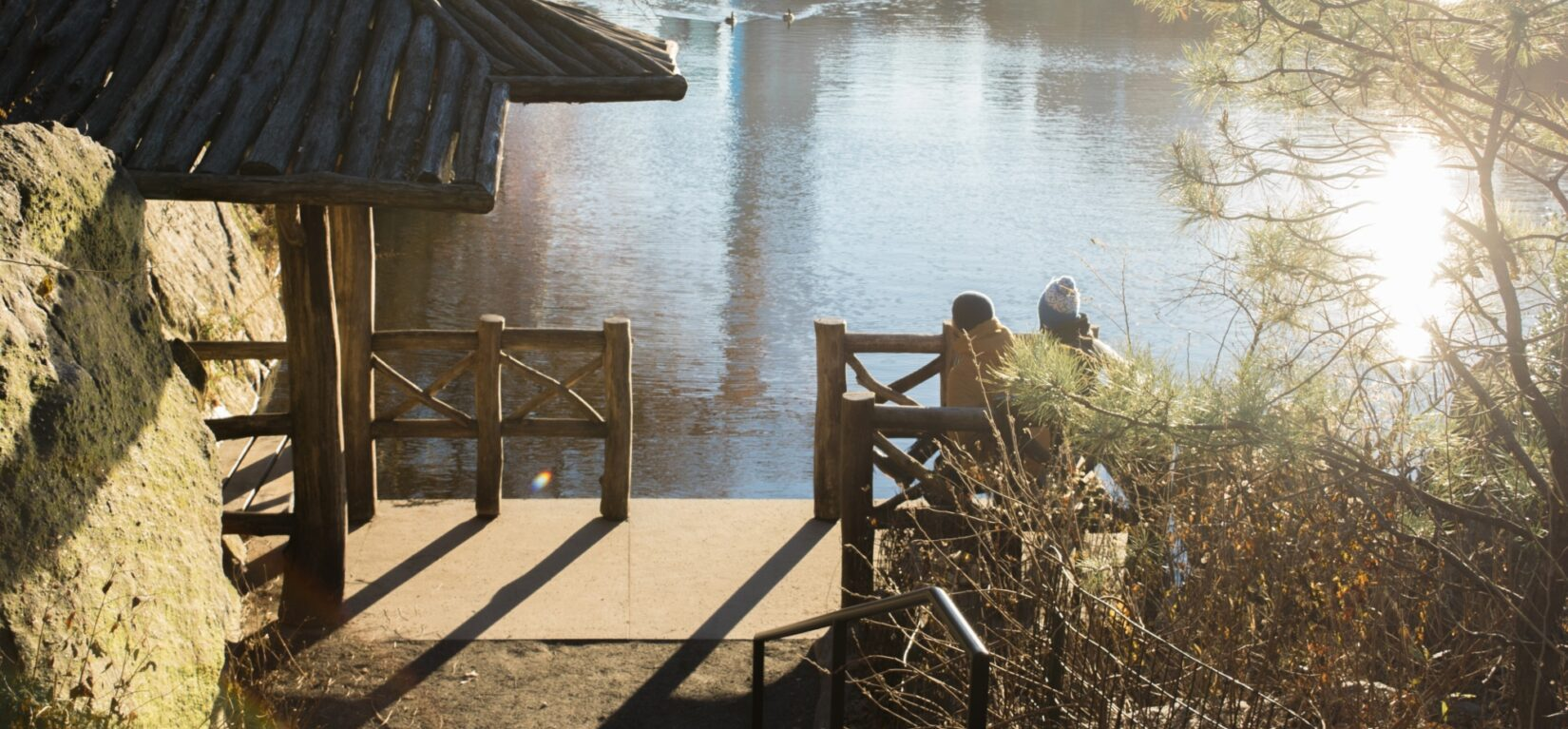 Two people enjoy a view of the Lake from a bench on the Chambers Boat Landing