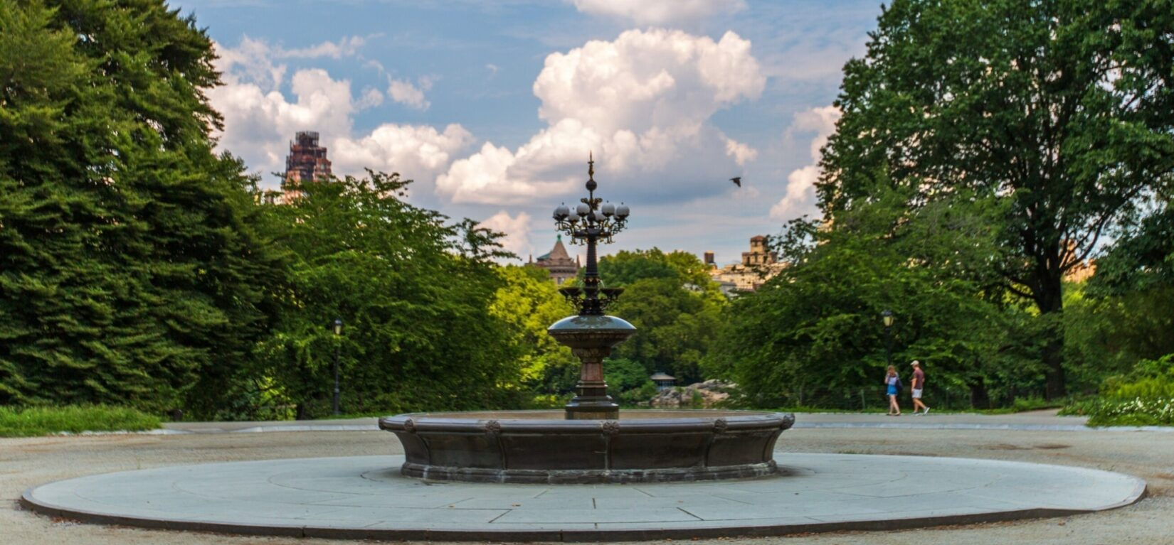 The fountain surrounded by a circular pathway lined with trees, under a blue sky with billowing clouds.