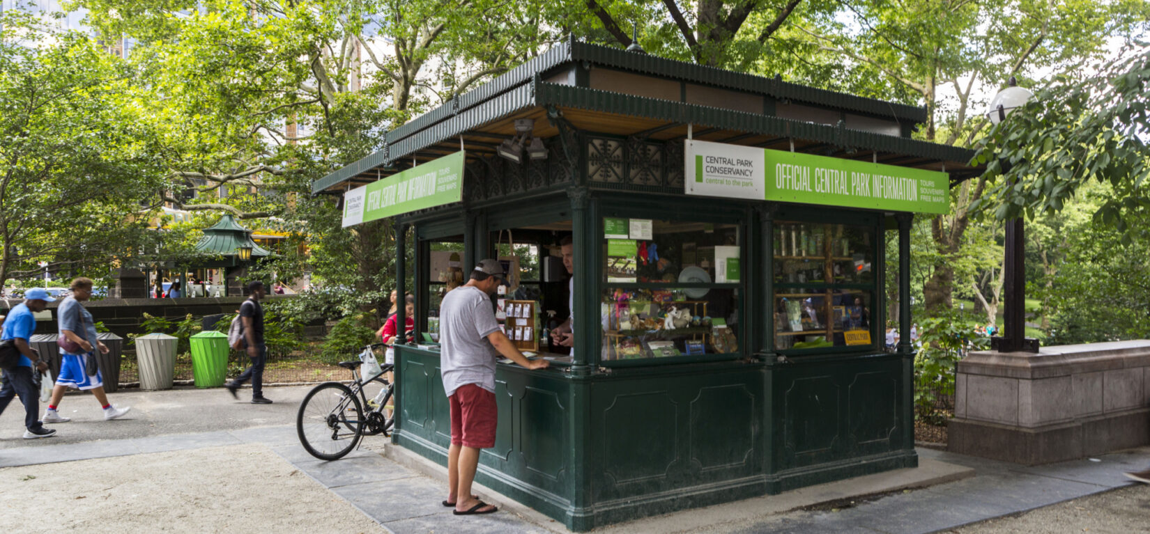 A patron at the kiosk, its windows open to a summer day