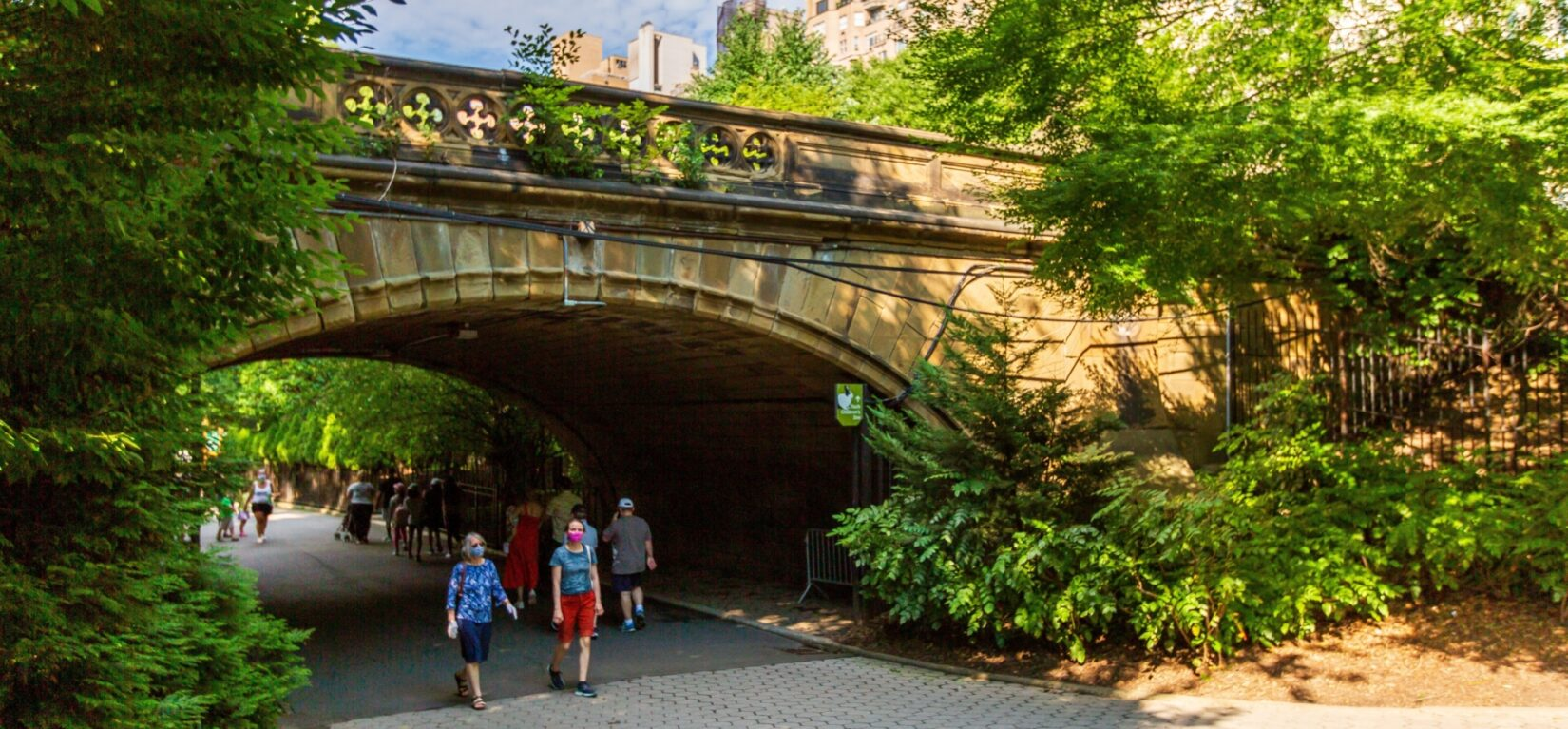 Visitors strolling beneath the Denesmouth Arch in summer