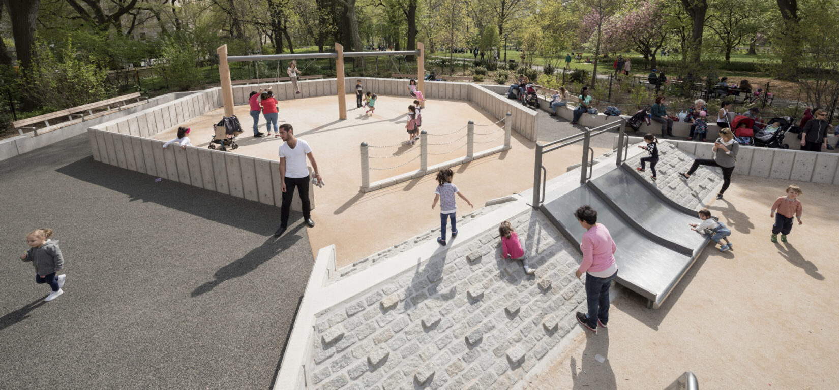 Children and caregivers enjoying the pyramid and slide in the playground