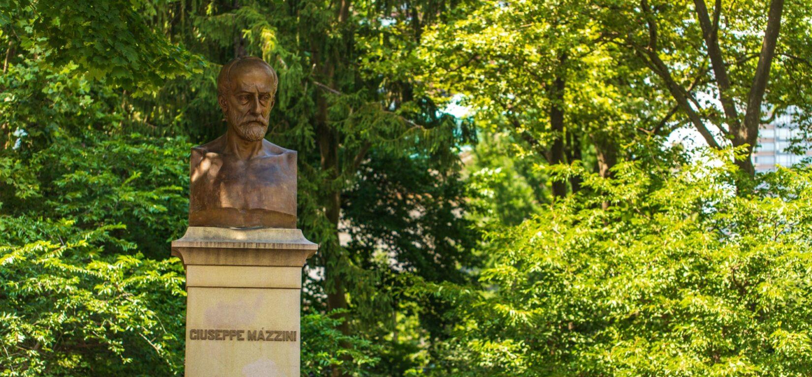 The bust of Giuseppe Mazzini on its pedastal under dappled shade