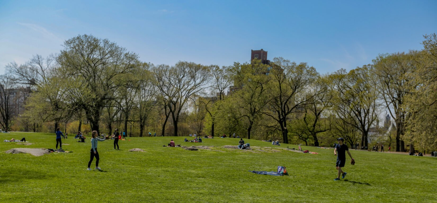 Visitors playing catch and catching rays on the Great Hill in spring