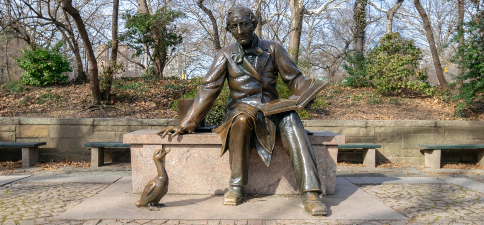 The statue shows the author with an open book on his lap and a duckling at his feet
