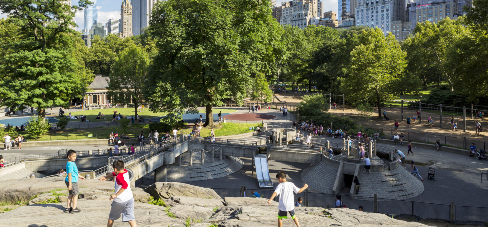 Children at play on the rocks at one end of the playground, with the skyline as a backdrop