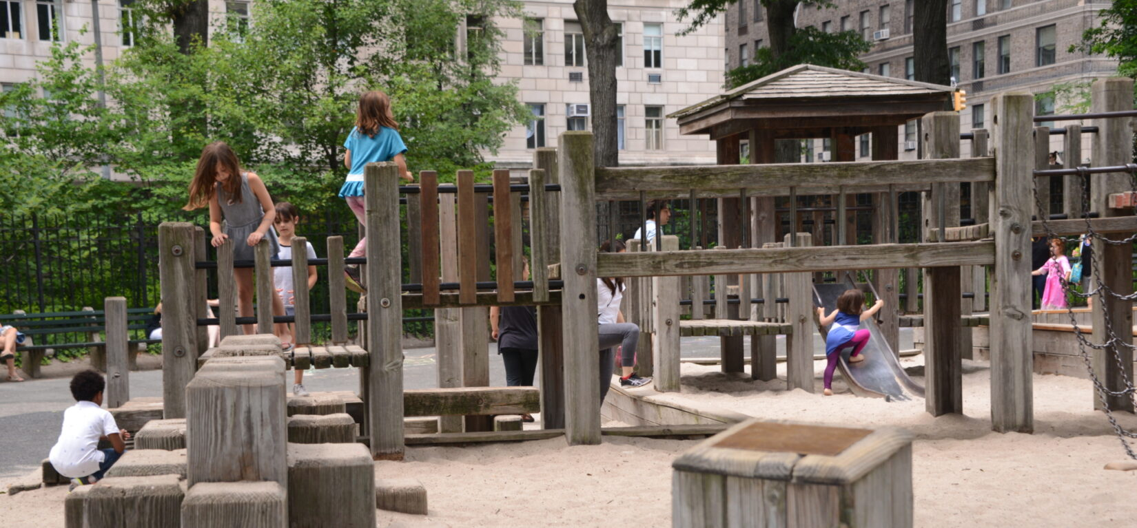 Small children clambor on the play structures