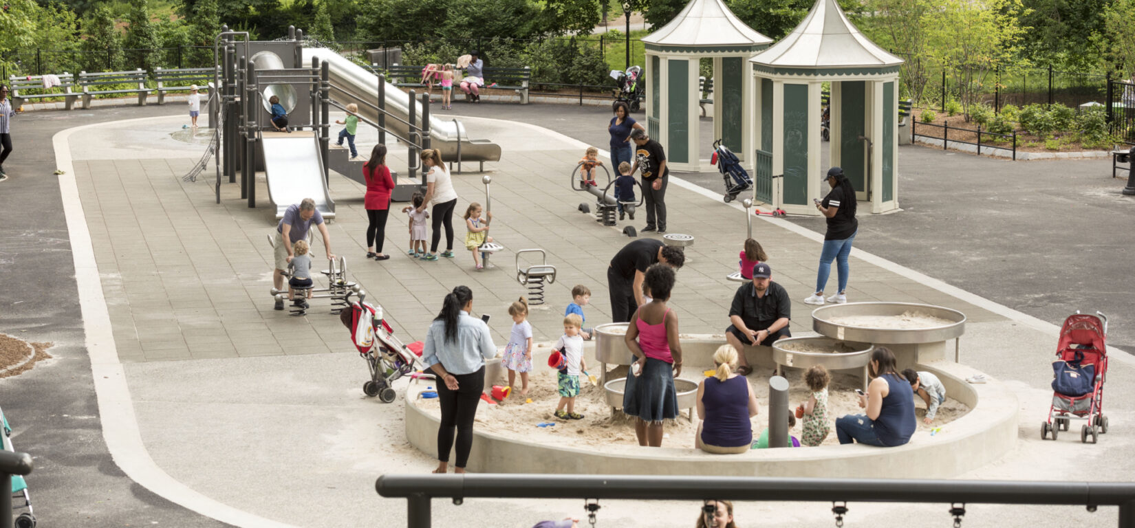Children and guardians enjoying the playground in summer