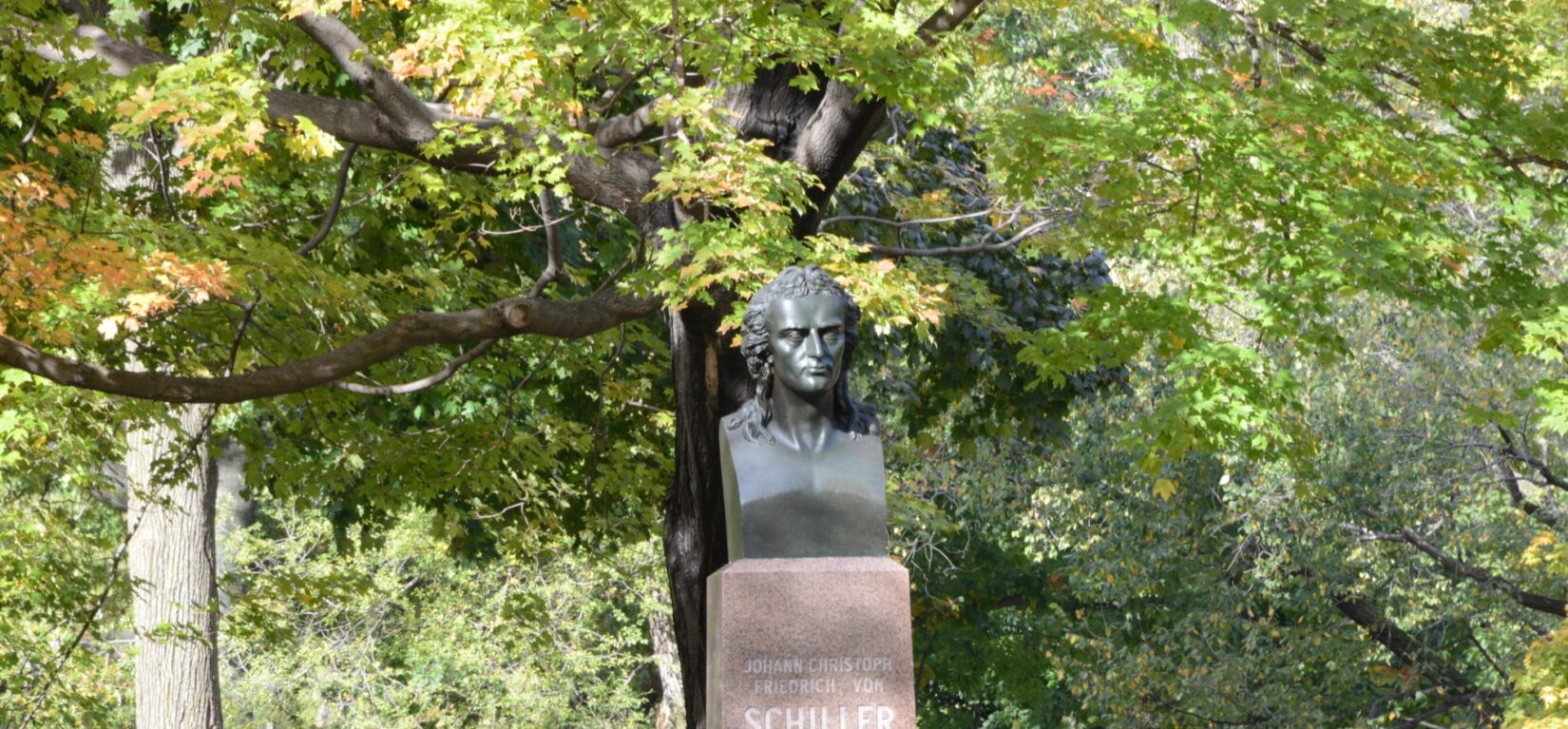 The bust of Schiller, on its pedestal, beneath the spreading branches of a tree