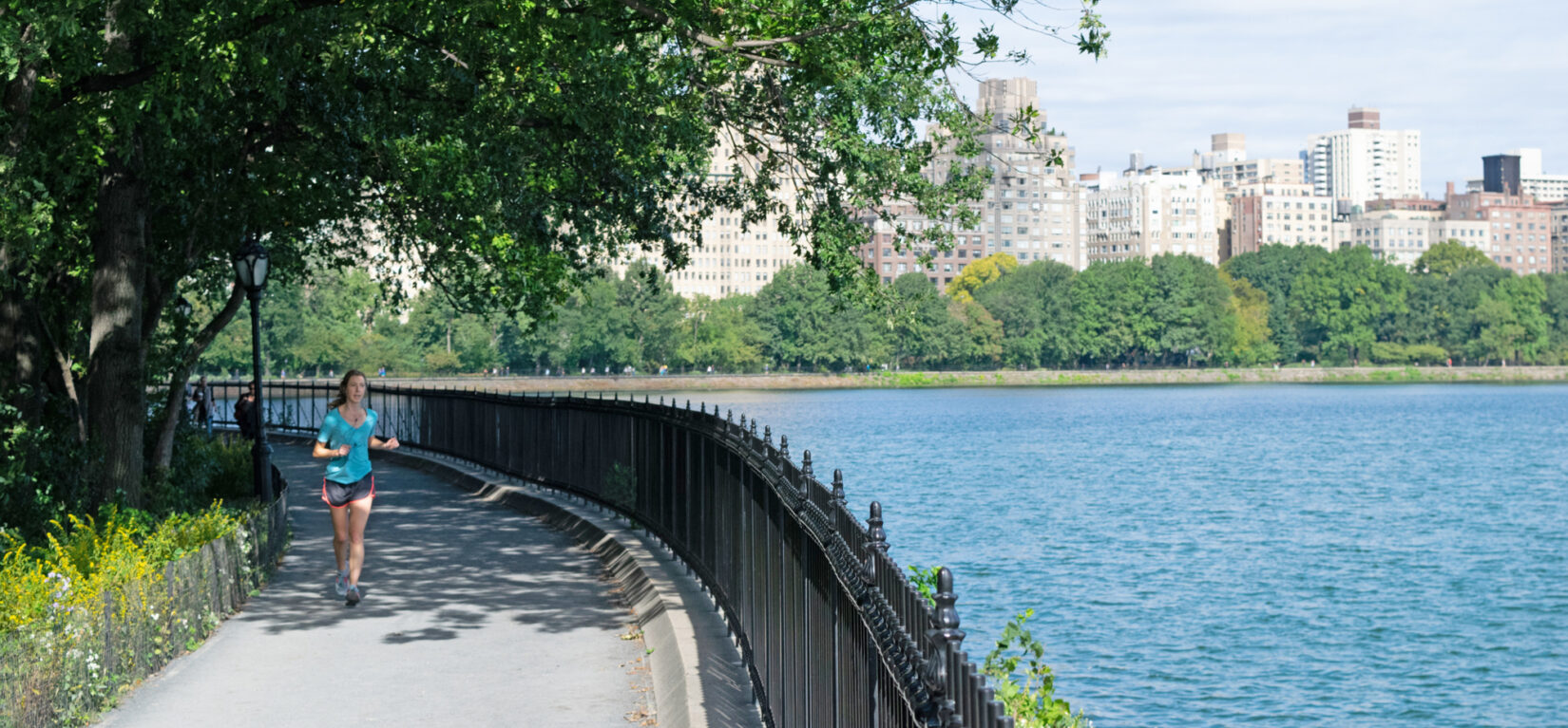 A woman jogs around the Reservoir on the Shuman Running Track