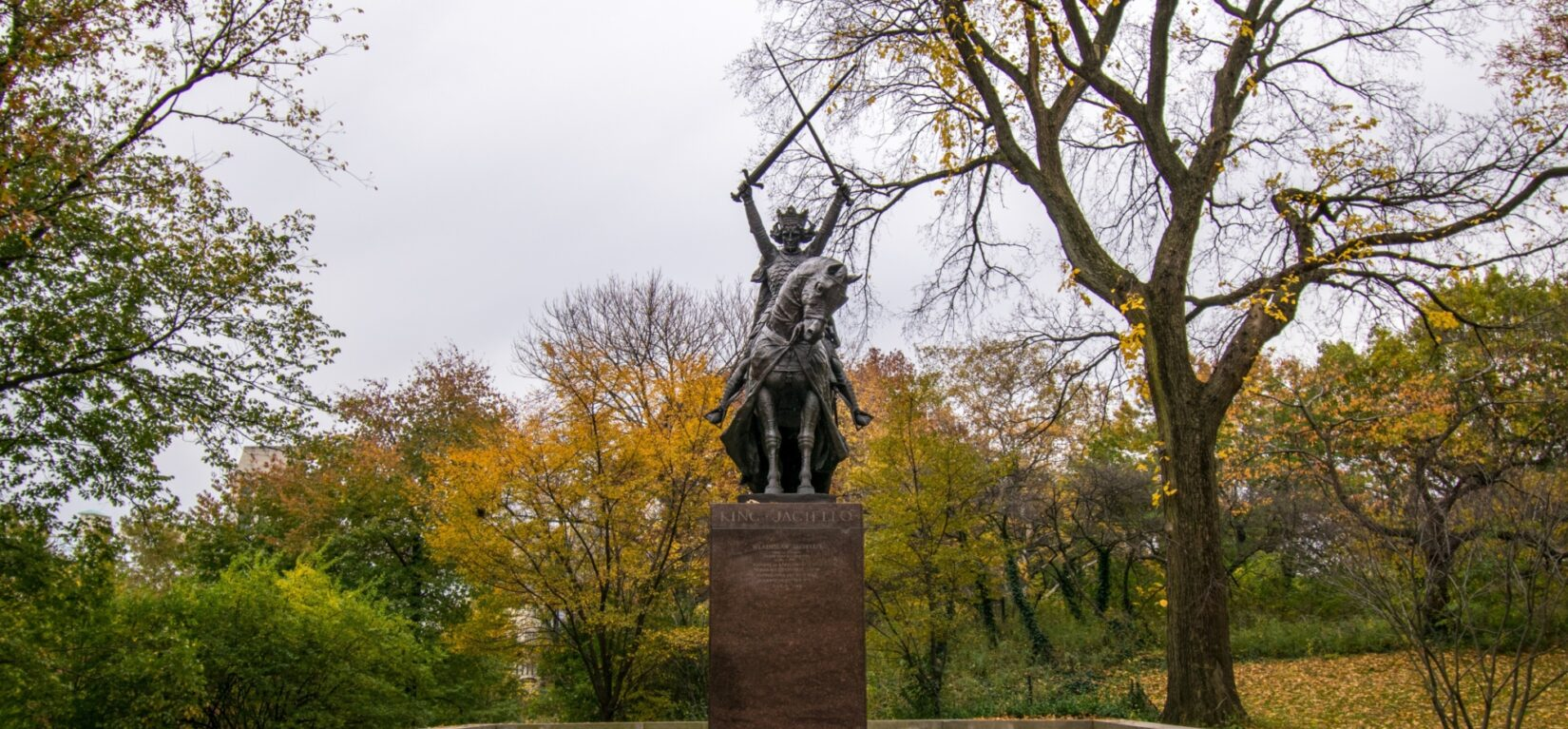 The King is seen astride his horse and holding two swords in his upraised hands